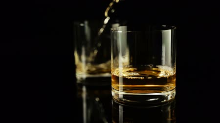 clear the table : Luxury whiskey poured to two empty glasses in slow motion