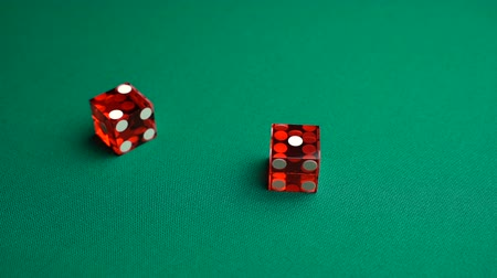 敗者 : The shooter rolls three in craps. Slow motion two red dice, craps, thrown on green tomentum background at casino, Ace Deuce. Gambling game with random result for adults.