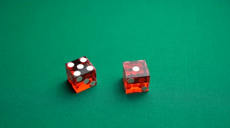 dobbelstenen : The shooter rolls the six in craps. Slow motion two red dice, craps, thrown on green tomentum background at casino, easy six. Gambling game with random result for adults.