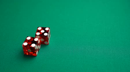 perdedor : The shooter rolls nine in craps. Slow motion two red dice, craps, thrown on green tomentum background at casino, Nina. Gambling game with random result for adults.