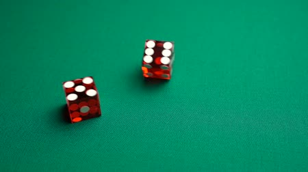 敗者 : The shooter rolls eleven in craps. Slow motion two red dice, craps, thrown on green tomentum background at casino, Yo or Yo-leven. Gambling game with random result for adults.