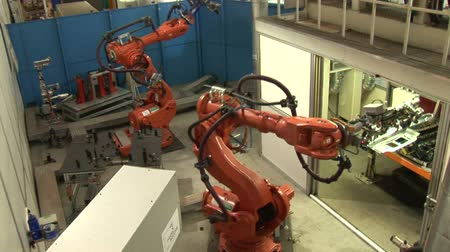 robots : Industrial Robots on an Assembly Line  Images of two industrial robots assembling auto parts. Hydraulic operating robotic arms in a factory.