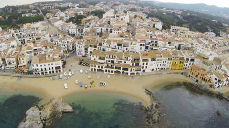 obec : Aerial Drone Fishing Village. Picturesque Mediterranean fishing village in la Costa Brava. Aerial drone shot flying over the rooftops to the old center of Calella de Palafrugell. Flying over turquoise beaches with a DJI Phantom.