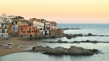 obec : Mediterranean Fishing Village at Dusk.  Picturesque Mediterranean fishing village in la Costa Brava, Girona. Typical Mediterranean landscape with white houses, tile roofs, wooden boats and pristine beaches. Dostupné videozáznamy