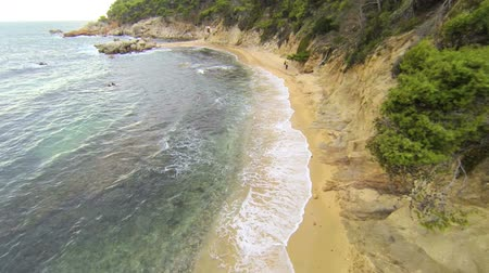 drone : Aerial drone Mediterranean beach.  Aerial video shot in a typical Mediterranean beach. Moving along the seashore over Stones, trees and sand with a DJI Phantom quad copter. Calella de Palafrugell beach in Girona, Catalonia. Stock Footage