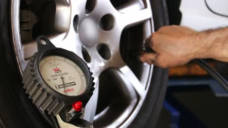 pneus : Car Repair Wheel Pressure.  Mechanic testing a car wheel pressure. Repairman taking the tire pressure with a pressure gauge.