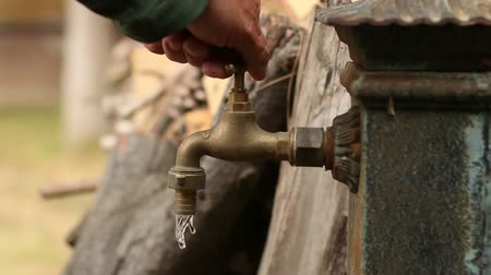 atık : Old Faucet. Dripping Tap.  Old faucet dripping. Iron fountain. A man opens and closes the tap. A good clip for ecology, energy saving, sustainability, water waste, domestic economy or saving money ideas.