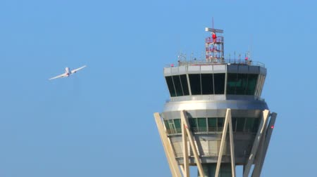управление : Airport Radar Control Tower.  Air Traffic Control Tower at Barcelona Airport with flying plane in sky. Airport control tower at full capacity. Radar control tower with an airplane across the sky.
