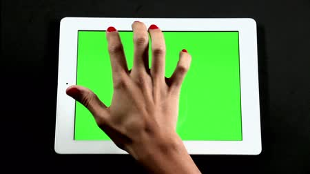 eszköz : Tablet Computer Touch Screen Finger Gestures on Green.  A finger taps and swipes on a screen touch to simulate interacting with a tablet computer device. Green screen ready for chroma key.
