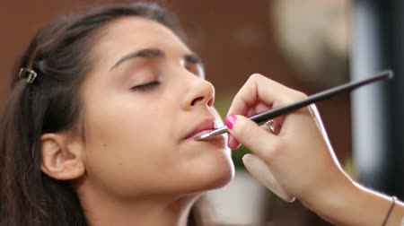 colocando : Face Makeup Making Lips Brush.  Young Mediterranean girl applying make up. Beautiful woman putting cosmetics. Gorgeous fashion and beauty care close up. Cosmetician making a beauty treatment to an elegance young girl closeups.