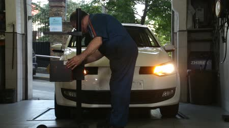 szerelő : Car Repair Mechanic Adjusting Headlights.  A repairman leveling headlights of a car. Car lights reparation and test. A mechanic testing headlights. Mechanic doing a car review.