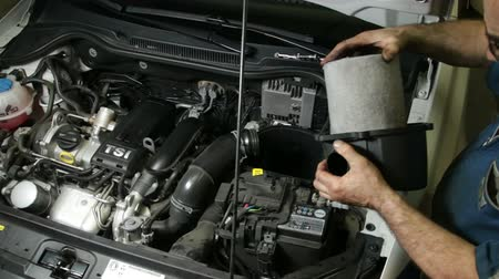 automobilový průmysl : Car Repair Mechanic Assembles Automobile Air Filter.  A repairman mounting the air cooling system of the engine. Car reparation and test. Mechanic doing a car review.