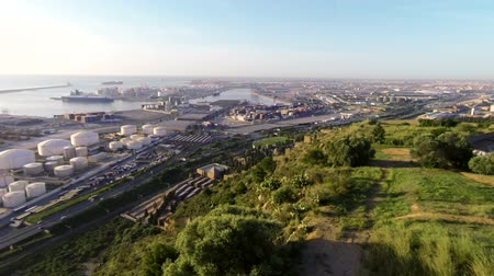 dron : Aerial Drone Barcelona Industrial Port.  Aerial view of the commercial port in Barcelona. A flight over the cemetery and the industrial harbor. Aerial shot over industrial zone next to a highway and a cemetery. Wideo