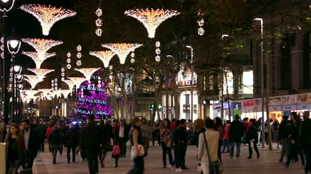 базарная площадь : Barcelona Christmas Street Lights Decorations.  Tourists walking and shopping in Barcelona at Christmas time. Christmas street color led lights decoration. Crowded Portal de l'Angel Street at night. Crowds shopping in Barcelona.