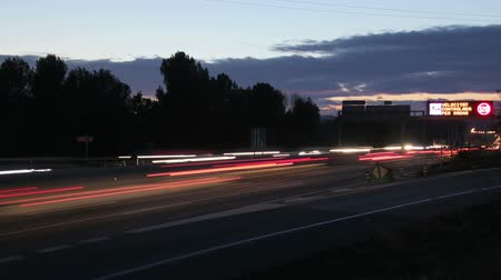 сумерки : Highway Traffic Cars at Sunset Time Lapse.  Highway with heavy traffic at rush hour. Lots of traffic at dusk. Cars driving at high speed. Gorgeous, high-energy roads time lapse.  Good for a video background. Great for any driving, corporate, city or urban