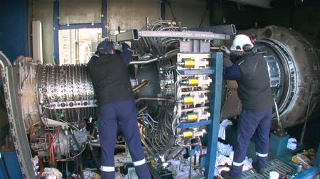 montaj : Engineers Repairing a Gas Turbine.  Repair and assembly of a turbomachine. Operators working in a gas turbine. Repairmen assembling high technology equipment. Stok Video