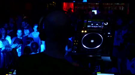 gece kulübü : Barcelona Night Disco Party Sala Apolo.  Turntable with people dancing in the background. People dancing in a fashion disco club in Barcelona. Dancing party clubbing at night. Music and flash lights. Colorful flash lights in the discotheque. Stok Video