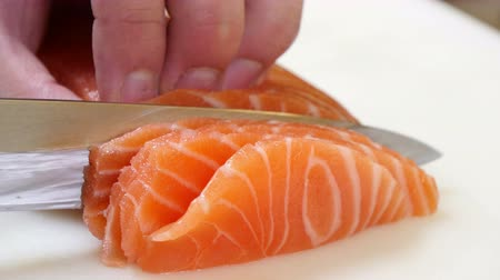 comida japonesa : Sushi Chef Slicing a Salmon Steak Nigiri Style.  A sushiman slicing a salmon steak with his Japanese knife. Preparing sushi nigiri fish. Japanese cuisine recipes. Professional chef with kitchen knives. Professional kitchen tools.