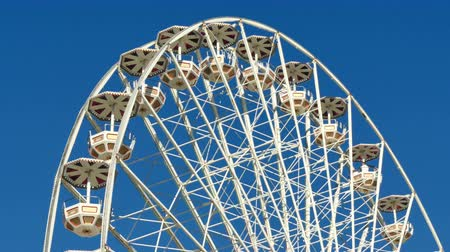 rekreace : Tall Classical Fair Ferris Wheel In France.  Ferris wheel on the banks of the Garonne River in Toulouse, France. Fair Ferris Wheel spinning at sunset. Fairground in France. Amusement park for children. Big recreation funfair for kids leisure time.