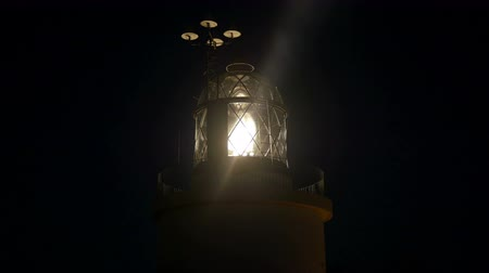 világítótorony : Maritime Lighthouse Flashing and Spinning at Night.  Mediterranean maritime lighthouse next to the sea. Navigation light at night. Lighthouse lamp turning on and spinning around. Light signaling for ships and boats.
