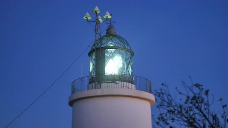 világítótorony : Maritime Lighthouse Start at Sunset.  Mediterranean maritime lighthouse next to the sea. Navigation light at night. Lighthouse lamp turning on and spinning around. Light signaling for ships and boats.