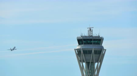 aninhada : Barcelona Airport Radar Control Tower.  Air Traffic Control Tower at Barcelona Airport with flying plane in sky. Airport control tower at full capacity. Radar control tower with an airplane across the sky. Vídeos