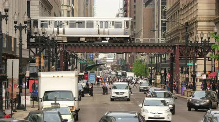 ingázó : Traffic on the Streets of Chicago Downtown.  Crowded Chicago city center of vehicles and pedestrians. Loop life on a weekday with the elevated underground trains crossing. Lots of cars and commuters in Illinois. Human activity on the streets of Chicago. Stock mozgókép