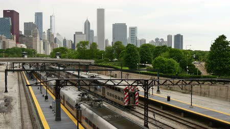 train workers : Trains Arriving and Leaving Chicago Loop District.  Metra train network in Chicago Downtown. Commuters traveling by train to their offices in the financial district of Illinois in the United States of America. Trains arriving at Chicago skyline early in t