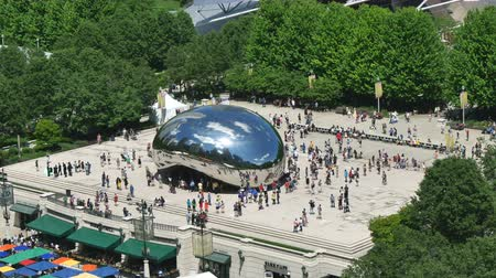 терраса : Tourists at the Chicago Bean Monument in Millennium Park.   Crowds visiting Millennium Park in Chicago. View from a skyscraper terrace in front of the park. Video showing a landmark in Illinois. Стоковые видеозаписи