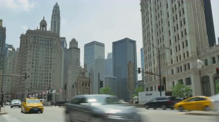 ingázó : Traffic on the Streets of Chicago Time Lapse.  Crowded Chicago city center of vehicles and pedestrians. Golden Mile life on a weekday at Michigan Avenue downtown district. Lots of cars and commuters in Illinois. Human activity on the streets of Chicago.