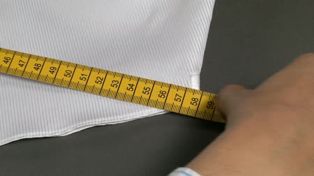 varal : Tailor Measuring Man Shirt Hips Width. Tailor measuring different parts on a mans shirt for its production. Measures for making mens shirts. Tailoring Jobs. Textile confection. Taking the steps to make a mans shirt.