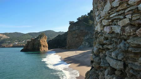sandy waters : Virgin Mediterranean Beach Steady Cam Flying Over the Cliff Rocks.  Typical Mediterranean beach in Spring digitally stabilized shot. Turquoise clear waters and golden sands during leisure time on the seaside. Waving waters on the sand beach and rocks. Stock Footage