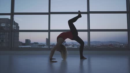 trained : Woman practicing yoga at sunset with city lights in background