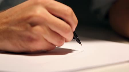 documentation : Man is drawing or writing on white sheet of paper. Macro shot of business wearing a shirt and writing on paper behind the desk Stock Footage