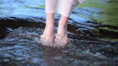 knöchel : Beautiful barefoot girl dipping her feet into fresh flowing river stream