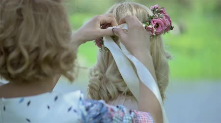 çelenk : Bridesmaid tying headband for beautiful blond bride on her wedding day. Bridal flower wreath on the head