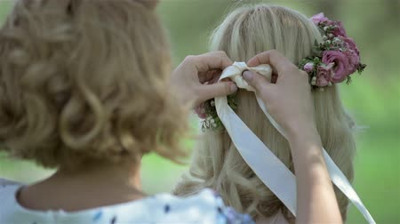 ティアラ : Bridesmaid tying headband for beautiful blond bride on her wedding day. Bridal flower wreath on the head