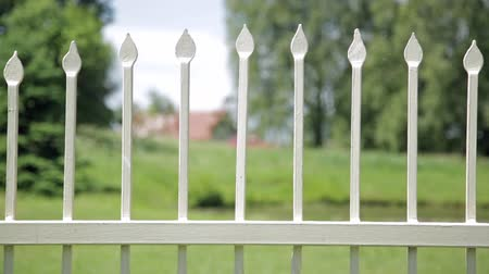 bariéra : Close up of antique wrought iron fence outdoors in the park. Shallow depth of field, spikes on fence