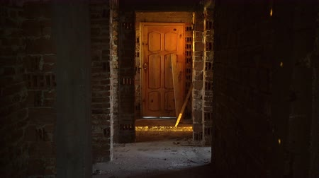 abandonar : Old, scary, abandoned house interior. Wooden door at the end of scary concrete corridor. Architecture structure Stock Footage
