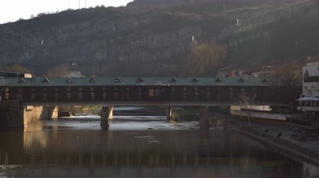 turistická atrakce : Pokrit most or Covered Bridge in Lovech, Bulgaria. Historic tourist attraction in old town of Lovech. Pedestrian bridge over Osam river with mountains in the background