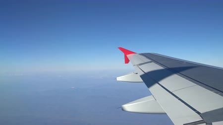 aeroespaço : Wing of an airplane flying above the morning clouds. Aircraft wing in the sky, looking through the window
