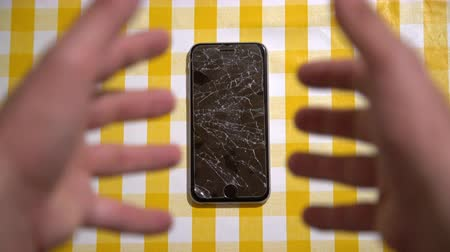 naufrágio : Concept of falling smart phone with broken screen. Top view on yellow desk background. Cracked, shattered lcd touch screen on modern cellphone. Gadget needs repairing Stock Footage