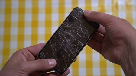 crashed : Concept of smart phone with broken screen. Top view of man hands holding a phone with cracked display. Cracked, shattered lcd touch screen on modern cellphone. Gadget needs repairing Stock Footage