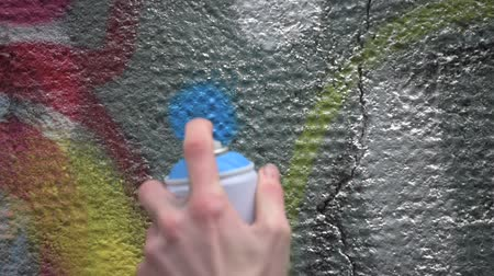ghetto streets : Graffiti artist in the street making art using spray paint on the concrete wall. Street art, urban culture Stock Footage
