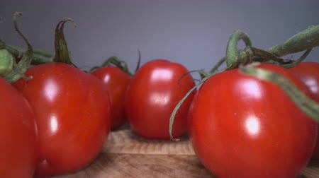 bezmotorové létání : Dolly shot of red cheery tomatoes on top of wooden table background. Gliding through home grown vegetables, healthy eating lifestyle