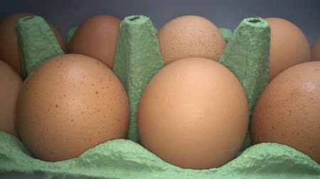 хрупкий : Gliding through two rows of brown eggs in cardboard box on white background. Chicken eggs in basket for sale