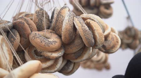 bécsi kifli : Hanging ring shaped rolls in a fare for sale on white background, bagels, bread ring with poppy seeds