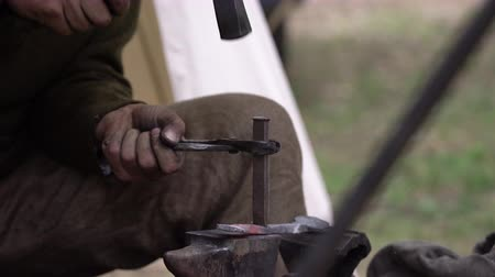 ручная работа : Blacksmith forging hot metal outdoors in his work shop. Craftsman hand forging metal outside