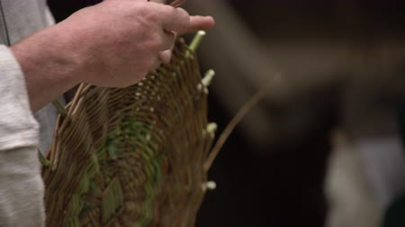 bamboo basket : Close up of craftsman wearing rural clothes making wicker basket of twigs. Traditional handmade weaving technique at rural village