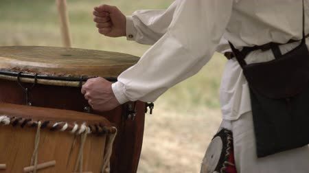 percussão : Man hands playing leather drum outdoors while wearing rural clothes. Traditional tribal drums performance